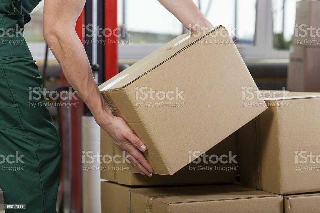 Hands of warehouse worker lifting box stock photo