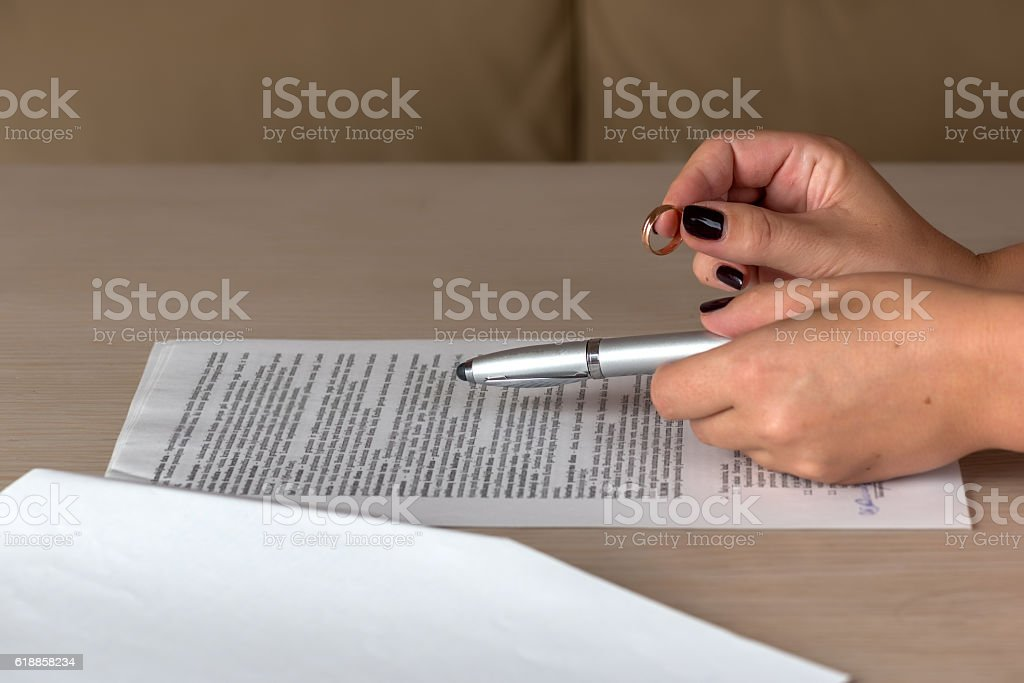 Hands of wife signing divorce documents, returning wedding ring stock photo