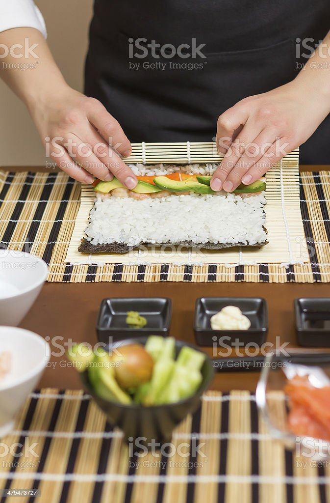 Hands of woman chef rolling up a japanese sushi stock photo