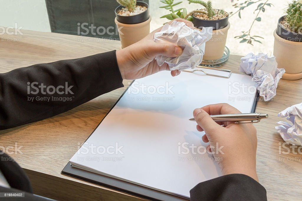 Hands of woman crumple sheets of Resume at the desk stock photo