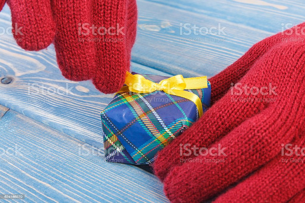 Hand of woman in red woolen gloves unpacking and opening colorful...