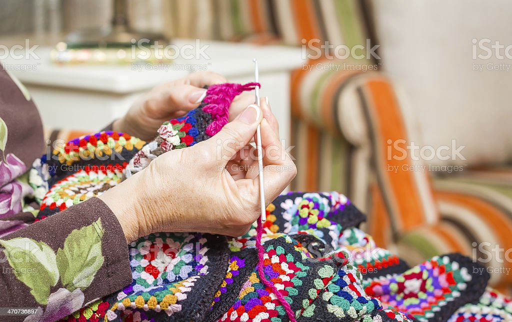 Hands of woman knitting a vintage wool quilt stock photo