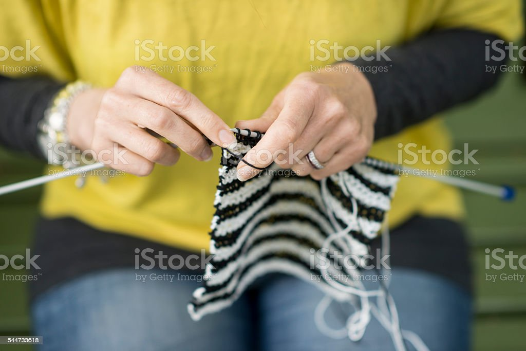 Hands of woman knitting outdoors. stock photo