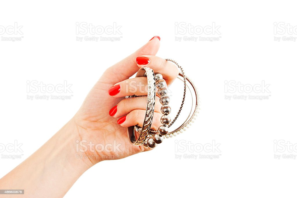 Hands of young woman holding many silver bangles stock photo