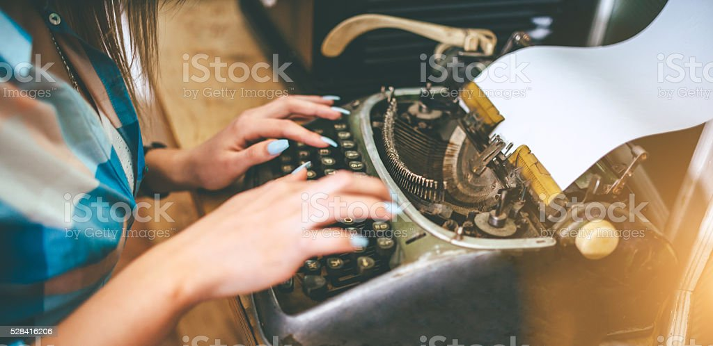 hands of young woman writer typing on antique typewriter stock photo