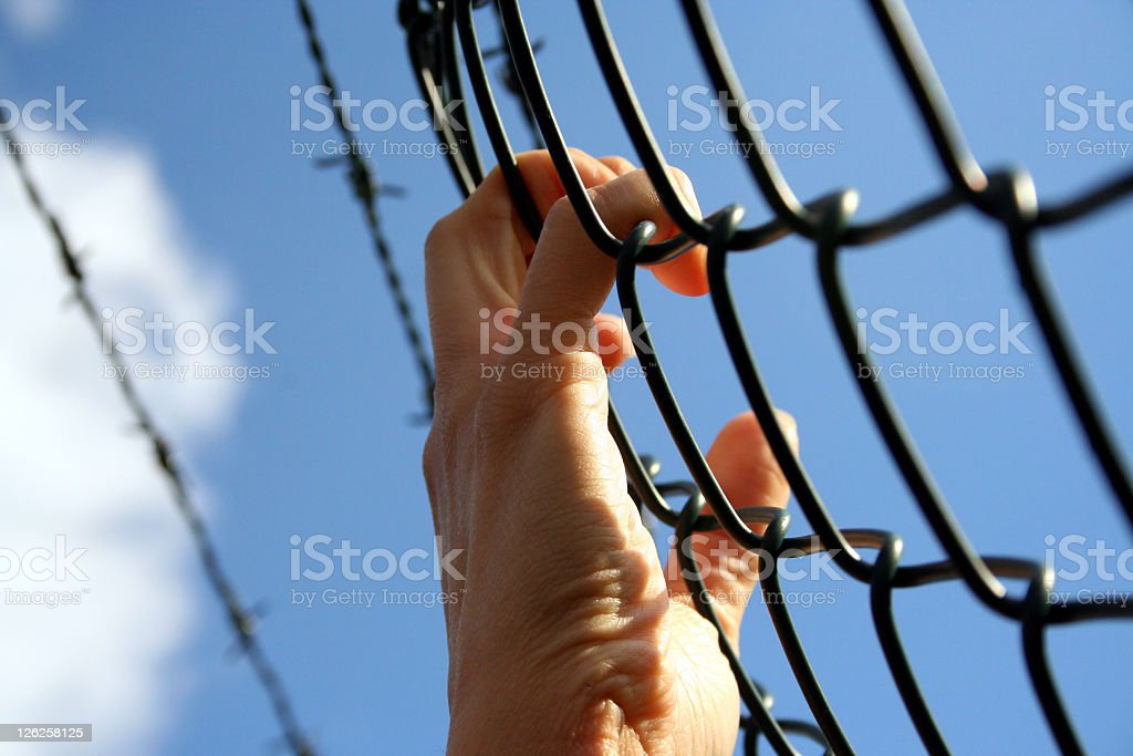 Hands on Barbed Wire - Craving Freedom Concept royalty-free stock photo