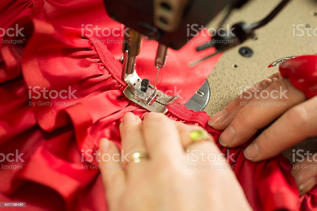 Hands on Cloth Fastened Through a Sewing Machine stock photo