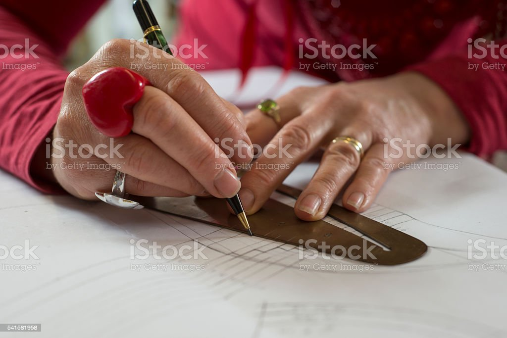 Hands on Curve Ruler and Pen Tracing Paper stock photo