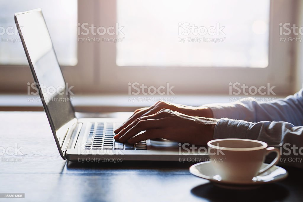 Hands on laptop keyboard stock photo