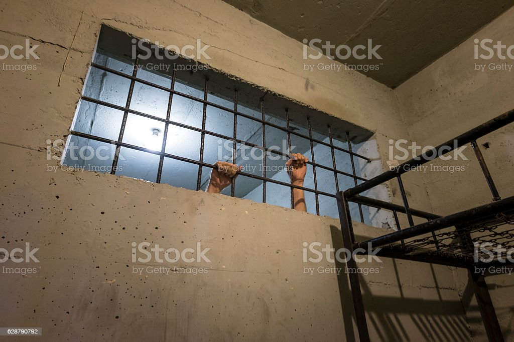 Hands on old jail cell window stock photo
