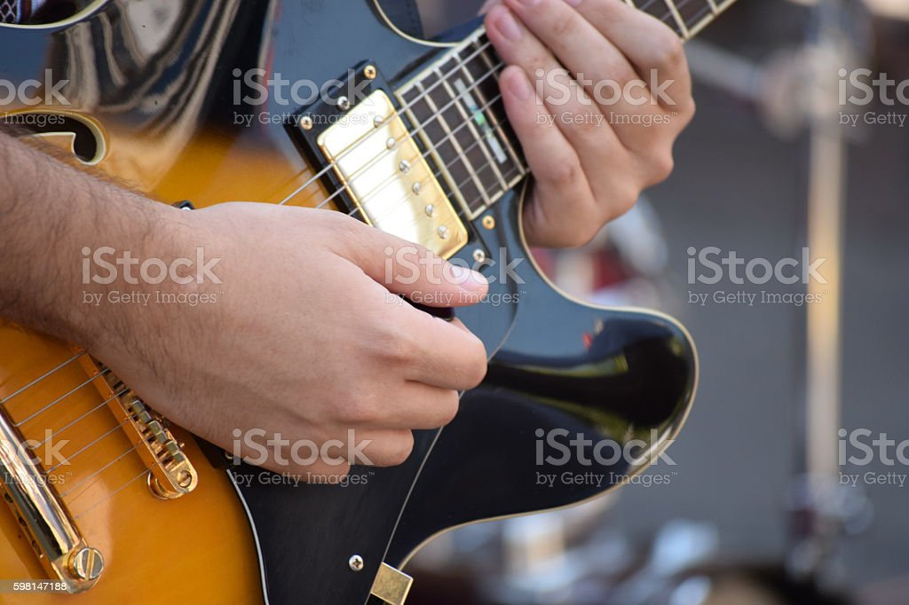 hands on the strings of electric guitars stock photo