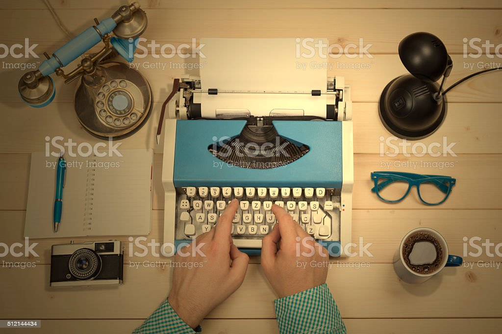 Hands on typewriter at the office desk. Flat lay. stock photo