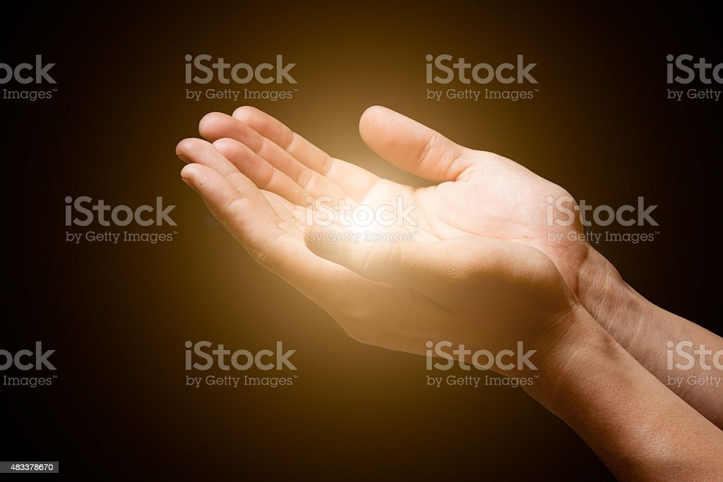 hands open with glowing lights stock photo