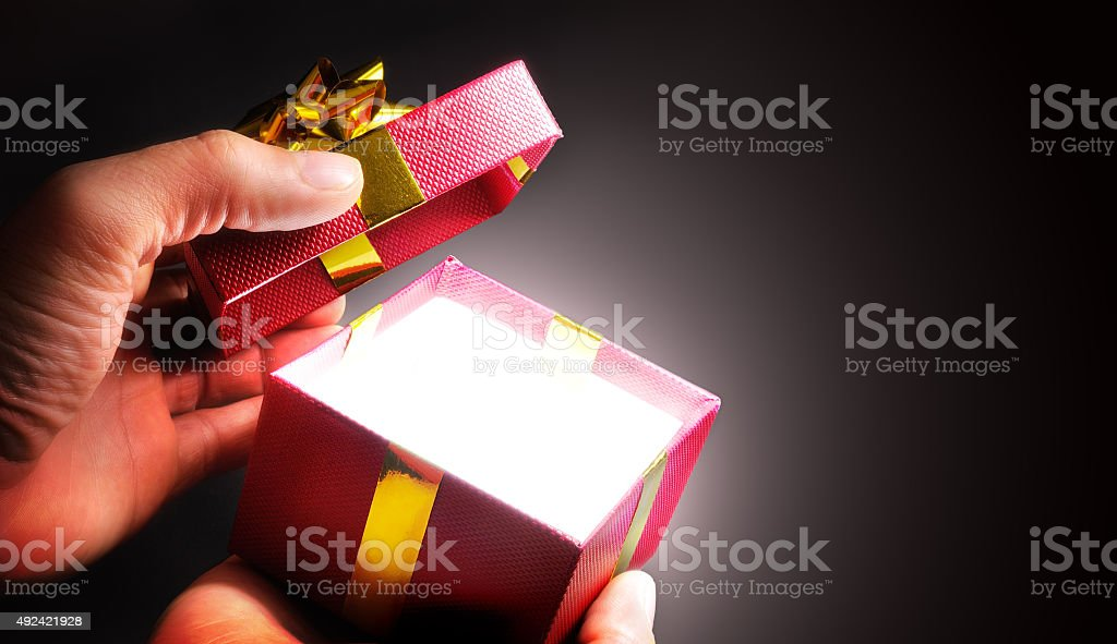 Hands opening a red gift box with ribbon in shadow stock photo