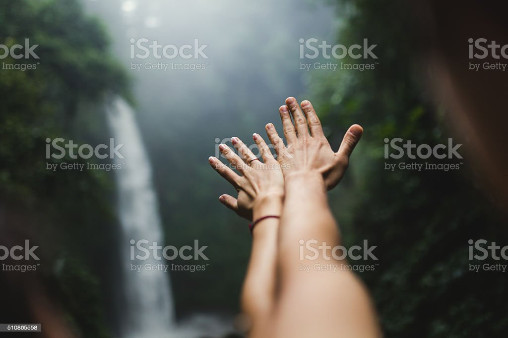 hands outstretched in the Waterfalls stock photo