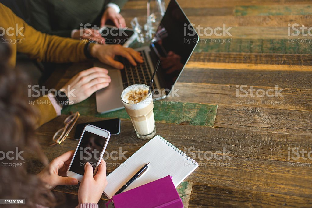 Hands over laptop smartphone tablet with coffee in trendy cafe stock photo