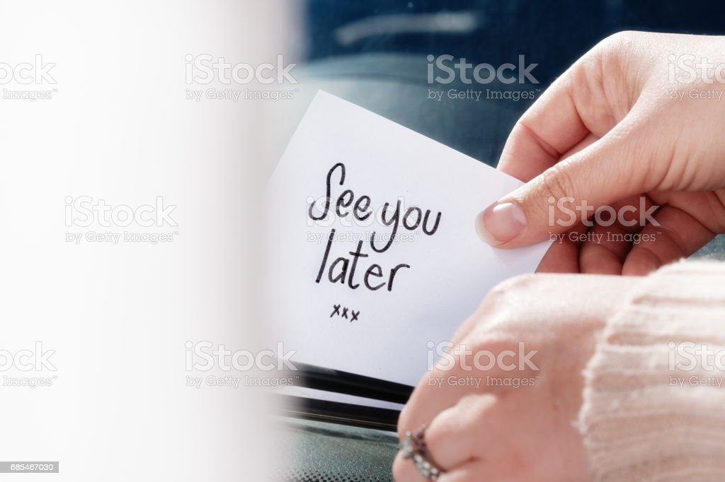 Hands place, or retrieve 'see you later' note on windshield stock photo