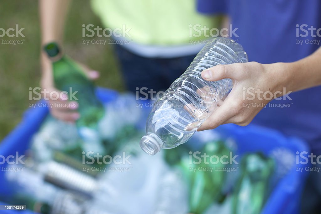 Hands placing bottles in recycling bin stock photo