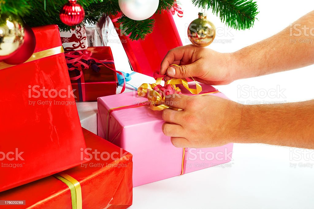 Hands placing gifts at the Christmas tree royalty-free stock photo