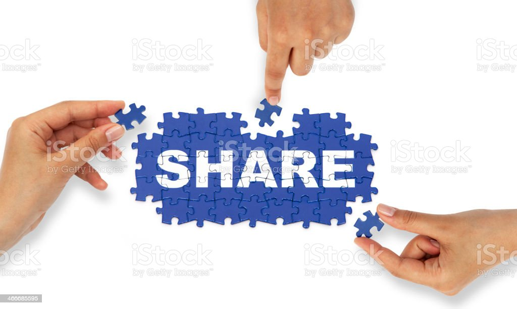 Hands placing jigsaw pieces together making the word share royalty-free stock photo