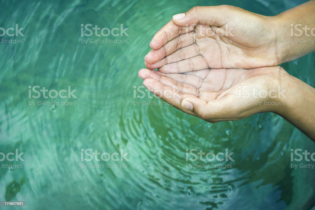 Hands playing with fresh water stock photo