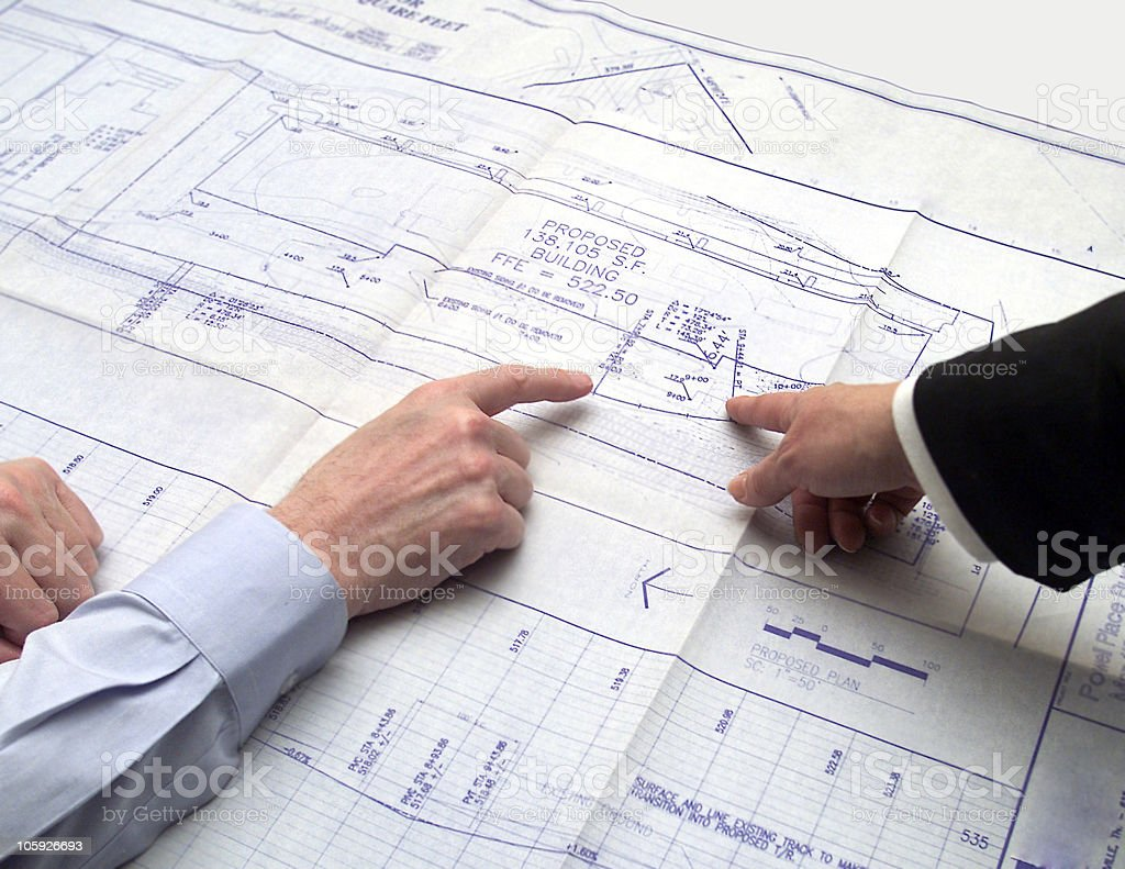 Hands Pointing to Blueprint royalty-free stock photo