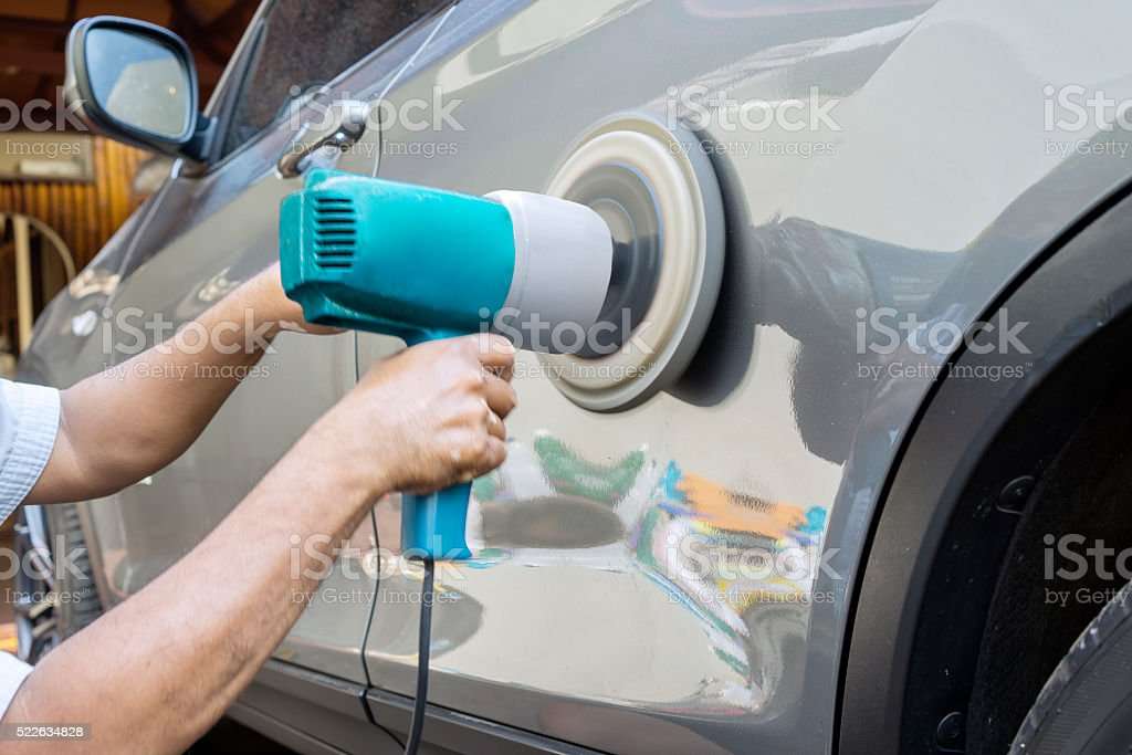 Hands polish a car body with polisher stock photo