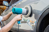 Hands polish a car body with polisher