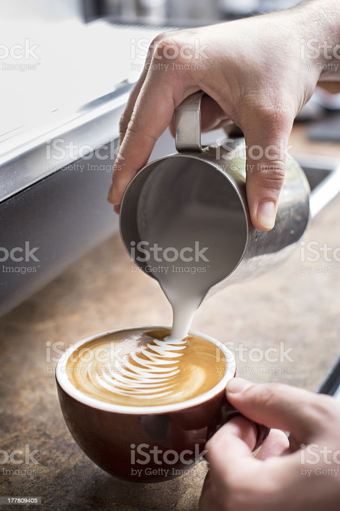 Hands Pouring Froth Art into a Cappucinno stock photo