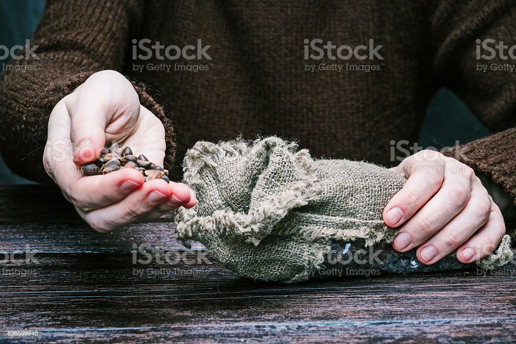 Hands pouring nuts into bag stock photo