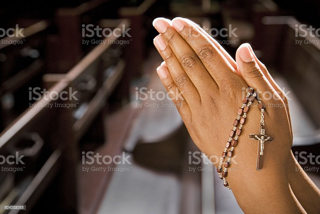 Hands Praying in Church With Rosary stock photo