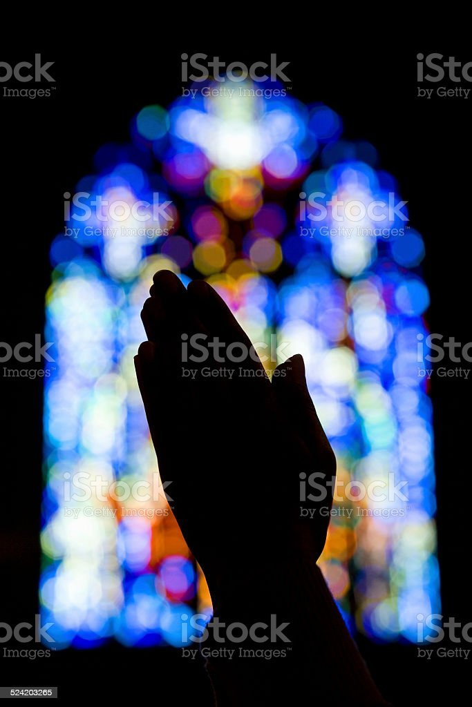 Hands Praying in Church With Stained Glass stock photo