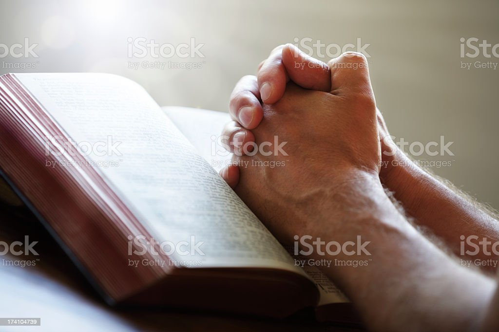 Hands praying on top of a Bible stock photo