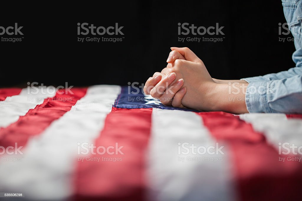 Hands praying over american flag stock photo