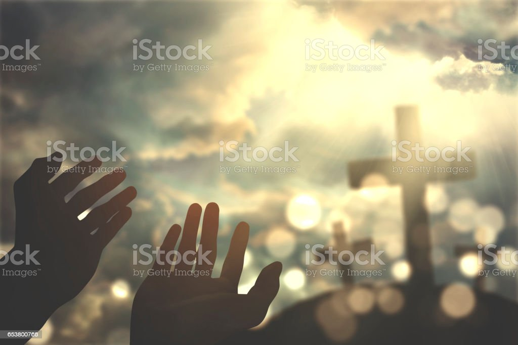 Hands praying with cross on sky stock photo