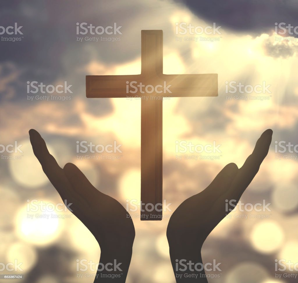 Hands praying with crucifix symbol stock photo