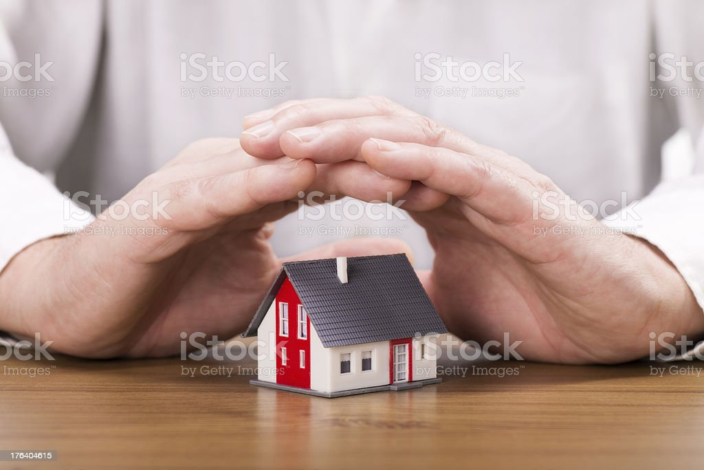 Hands protecting a house stock photo