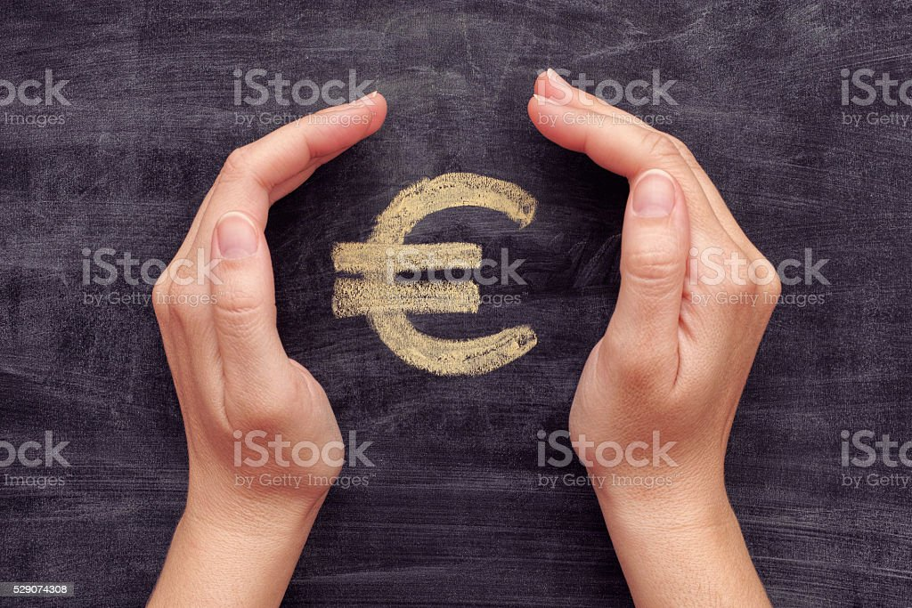 Hands protecting drawn euro sign on black chalkboard background stock photo