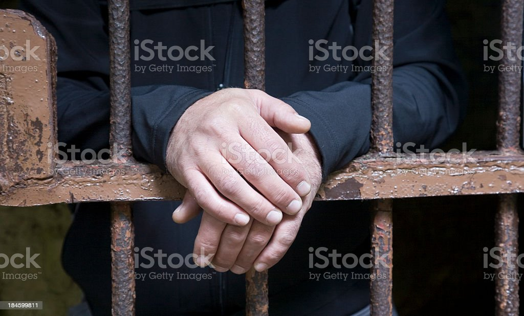 Hands protruding from jail cell bars stock photo