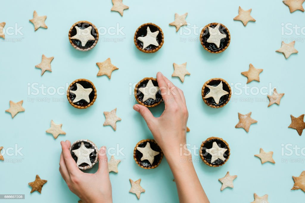 Hands put star shaped tart on mint color background, top view stock photo