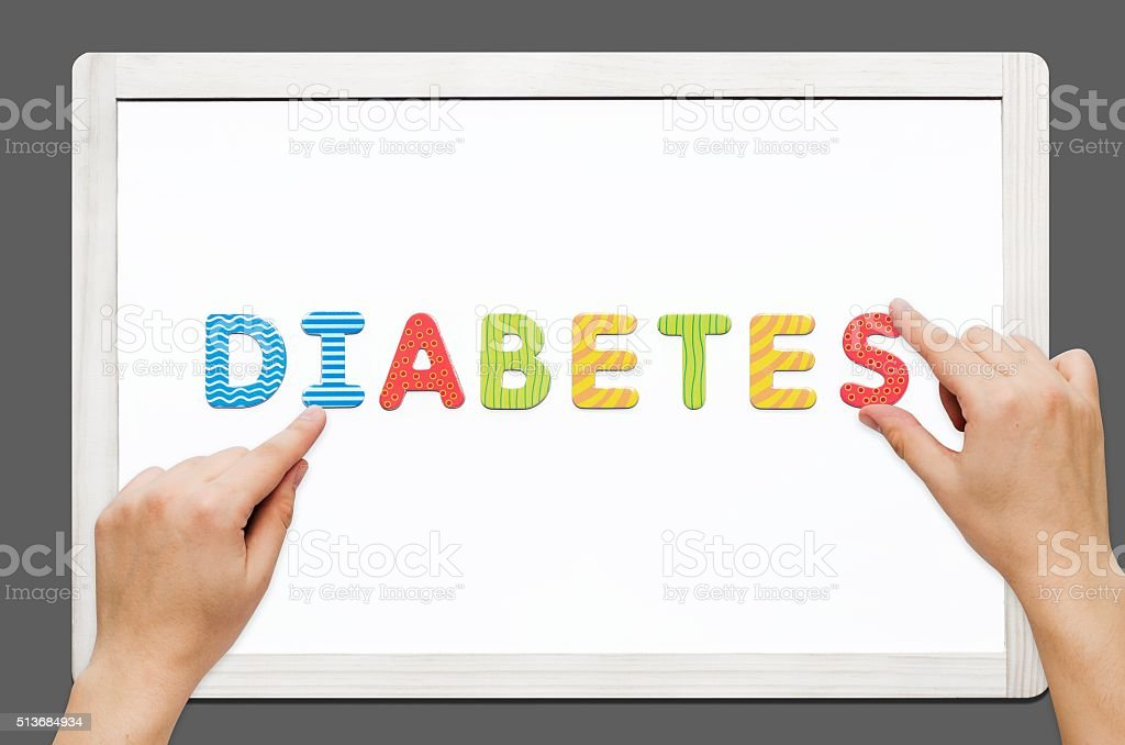 Hands put the word Diabetes with magnetic letters stock photo