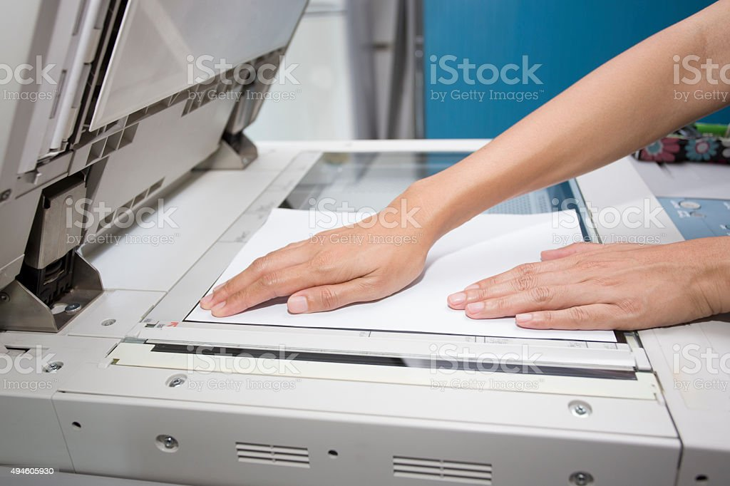hands putting a sheet of paper into a copying device stock photo