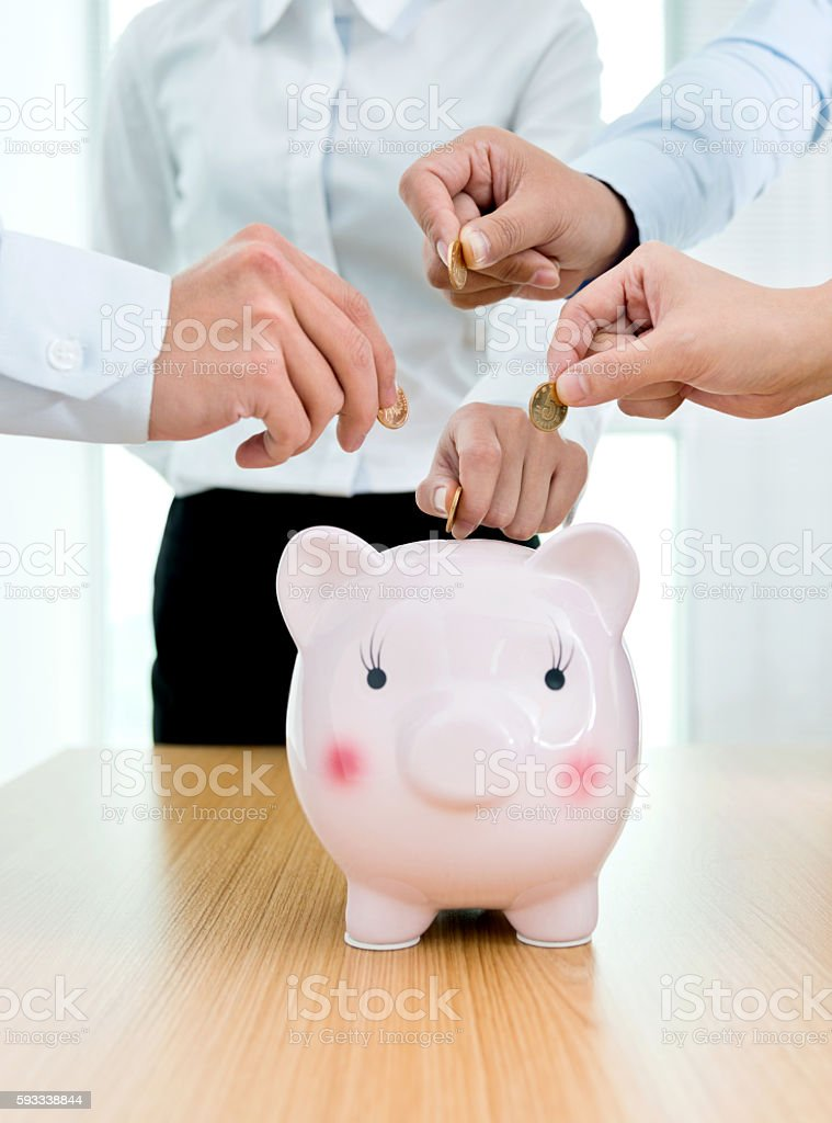 Hands putting coin to piggy bank stock photo