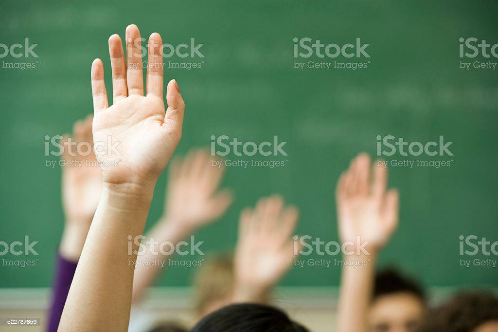 Hands raised in classroom stock photo
