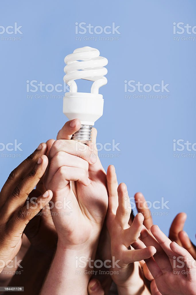 Hands reach for unlit compact fluorescent light bulb royalty-free stock photo