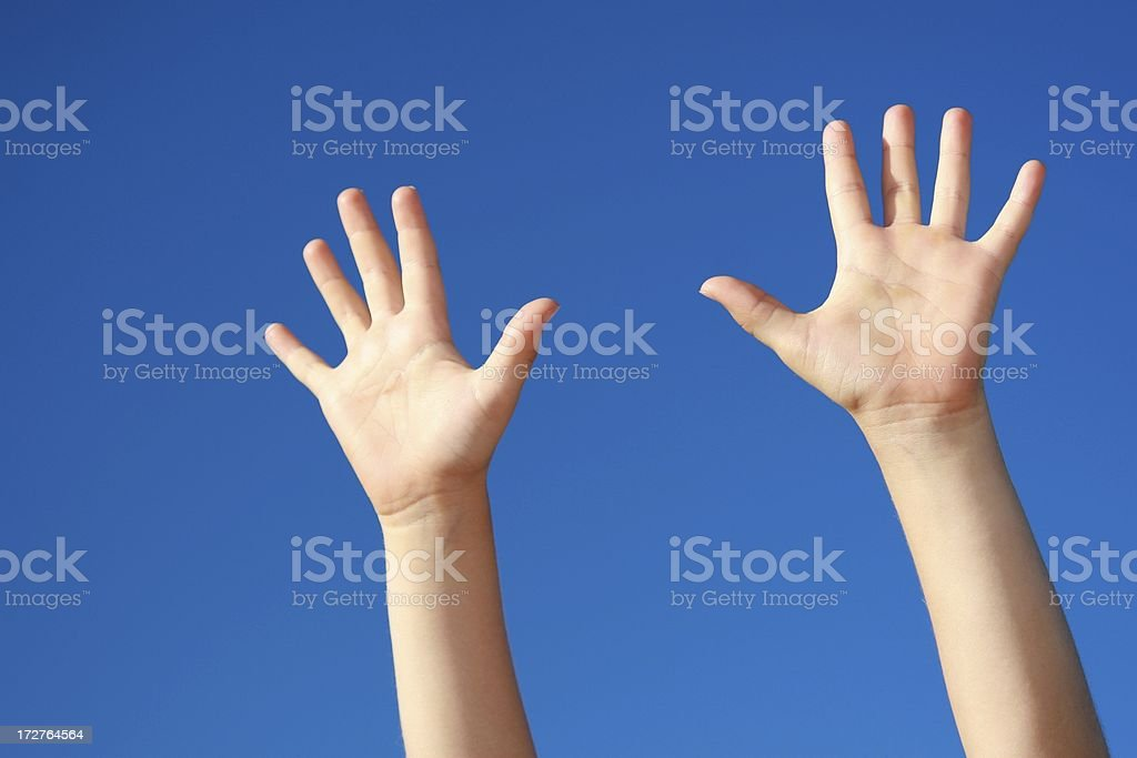 Hands Reaching Up on blue sky background stock photo