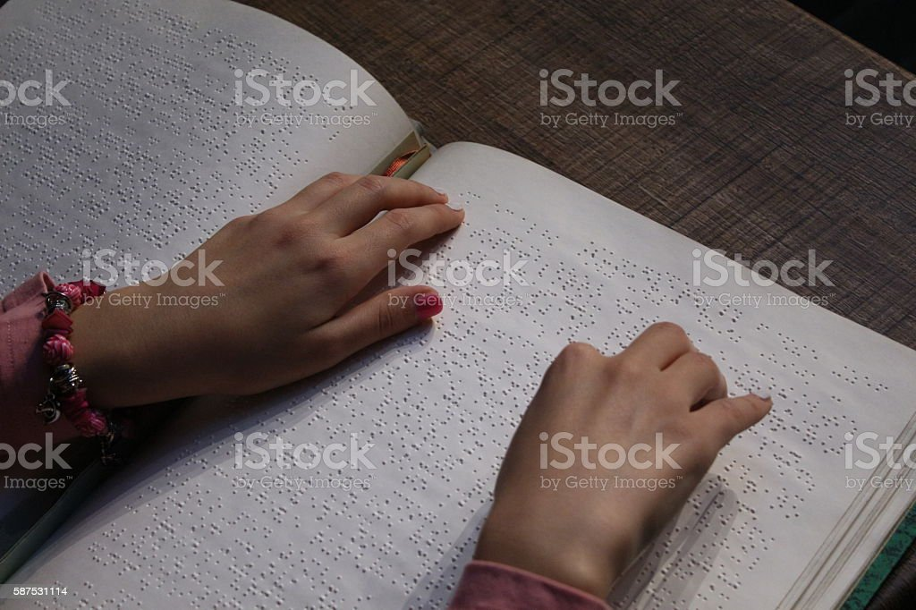 Hands reading a braille book stock photo