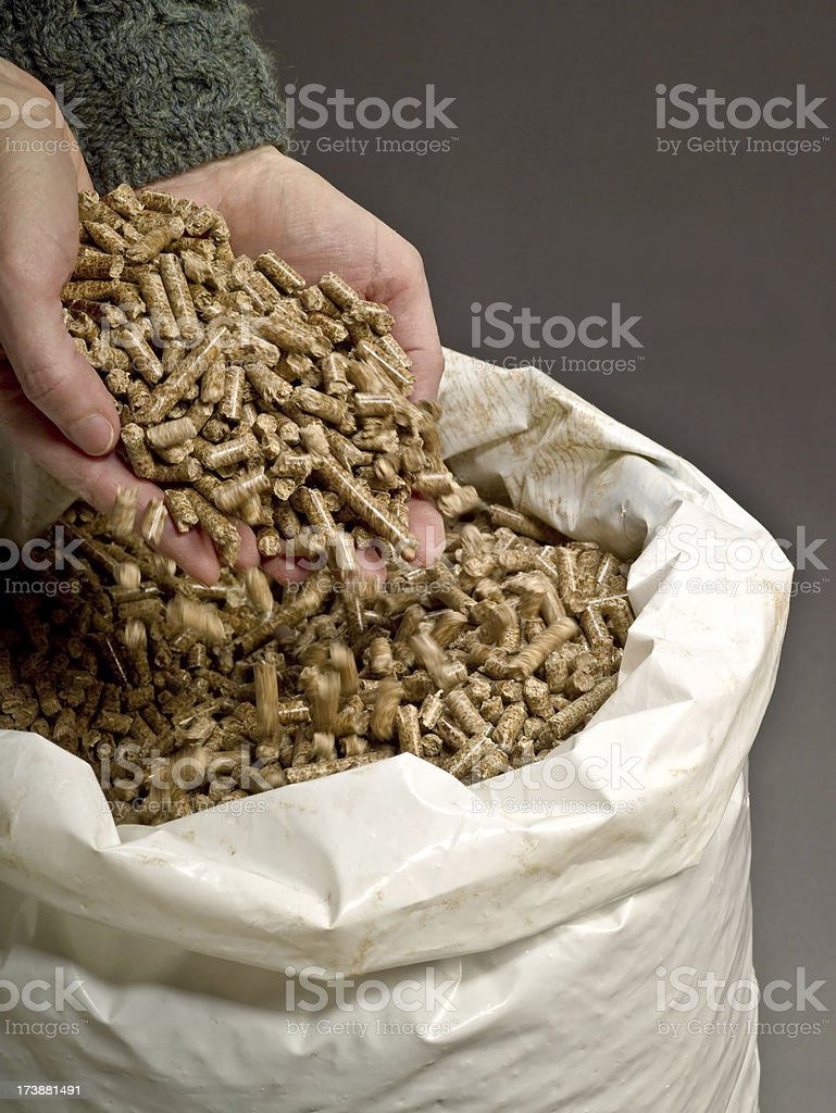 Hands releasing wood pellets back stock photo