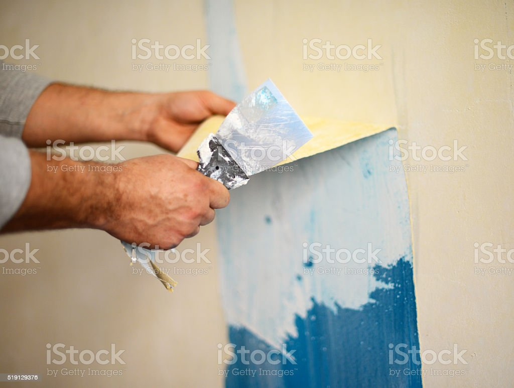 Hands removing wallpaper stock photo