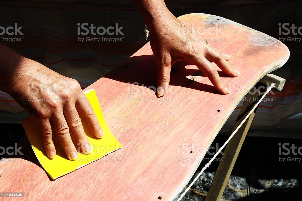 Hands restoring an old skateboard with yellow sandpaper stock photo